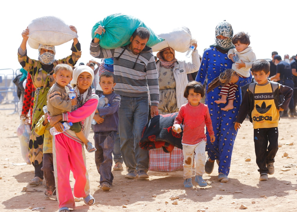 Kurdish Syrian refugees walk at the Turkish-Syrian border near the southeastern town of Suruc in Sanliurfa province, September 24, 2014. The United Nations refugee agency said on Tuesday it was making contingency plans in case all 400,000 inhabitants of the Syrian Kurdish town of Kobani fled into Turkey to escape advancing Islamic State militants.      REUTERS/Murad Sezer (TURKEY  - Tags: POLITICS CIVIL UNREST CONFLICT)   - RTR47HI4