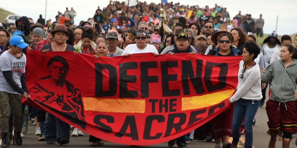 Native Americans march to the site of a sacred burial ground that was disturbed by bulldozers building the Dakota Access Pipeline (DAPL), near the encampment where hundreds of people have gathered to join the Standing Rock Sioux Tribe's protest of the oil pipeline slated to cross the nearby Missouri River, September 4, 2016 near Cannon Ball, North Dakota. Protestors were attacked by dogs and sprayed with an eye and respiratory irritant yesterday when they arrived at the site to protest after learning of the bulldozing work. / AFP / ROBYN BECK (Photo credit should read ROBYN BECK/AFP/Getty Images)