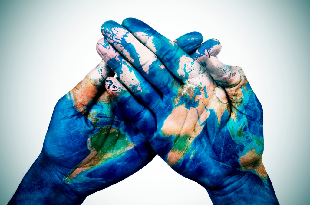 man hands patterned with a world map (furnished by NASA)
